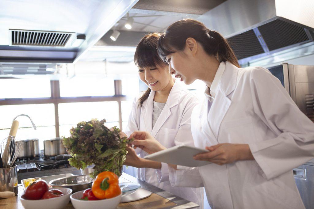 栄養士たちが野菜とタブレットを片手に分析し